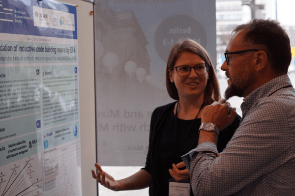 MQIC participants discussing in front of a poster
